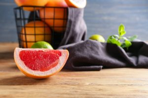 Fresh grapefruits and limes on wooden table