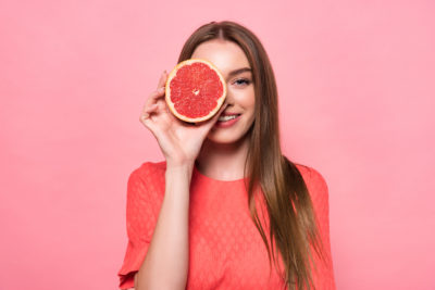front view of attractive smiling young woman holding cut grapefruit isolated on pink