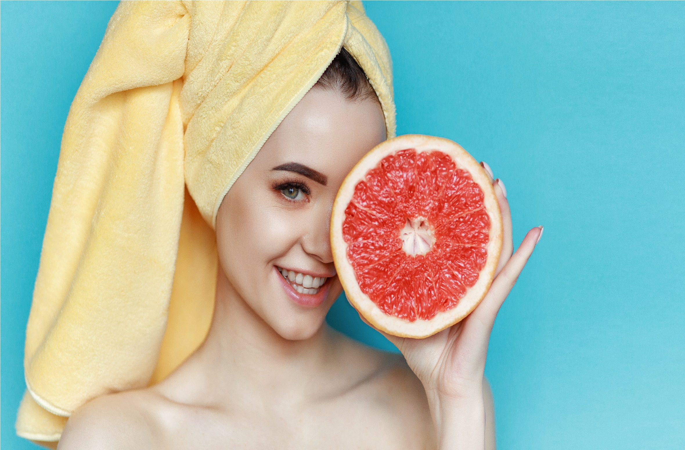 Portrait of young beautiful woman with healthy glow perfect smooth skin holds piece of grapefruit, closing one eye. Natural cosmetics, skincare, wellness, facial treatment, cosmetology concept.