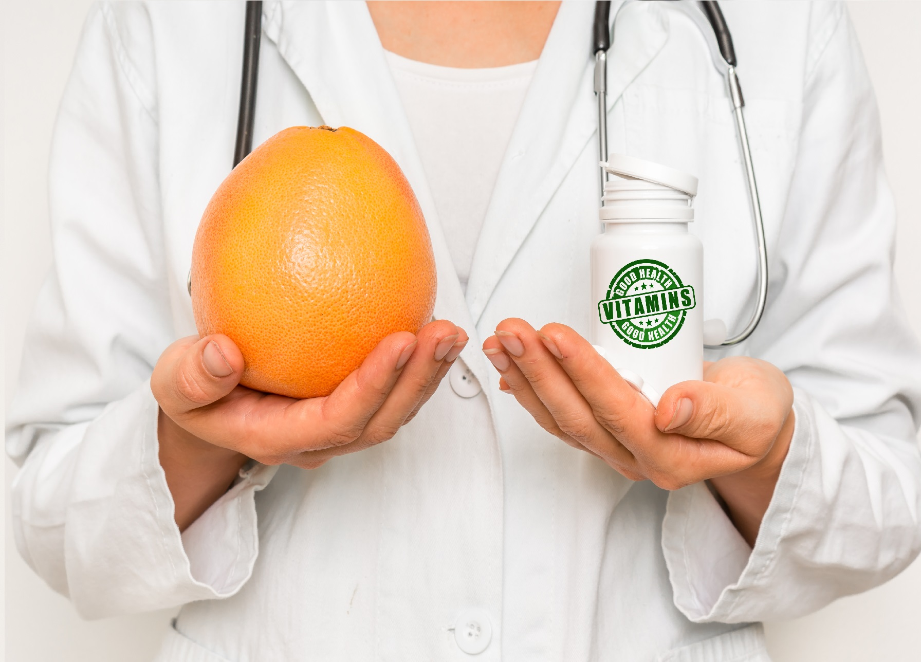 Female doctor compare pile of pills with fresh grapefruit